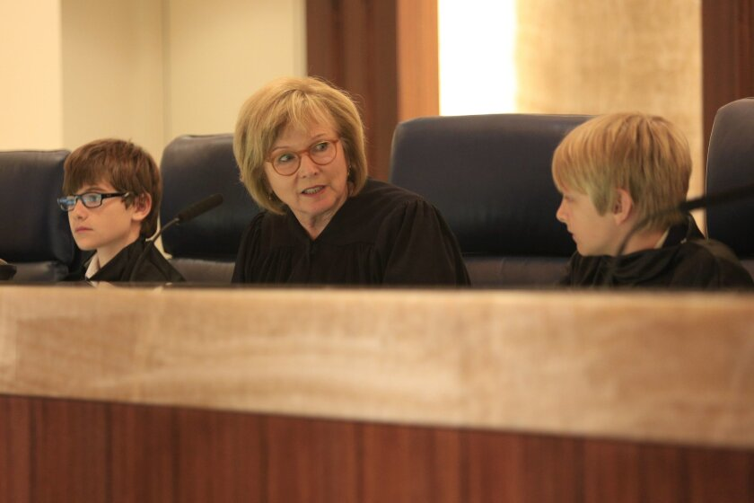 Presiding Appellate Justice Judith McConnell is flanked by students from El Camino Creek Elementary School who played the part of justices on the U.S. Supreme Court in a mock trial. Sixth graders from the school descended on the Court of Appeal for the Fourth Appellate District, in downtown San Diego to re-enact author Yoshiko Uchida's account of Fred Korematsu's legal challenge to Japanese internment policies during World War II,