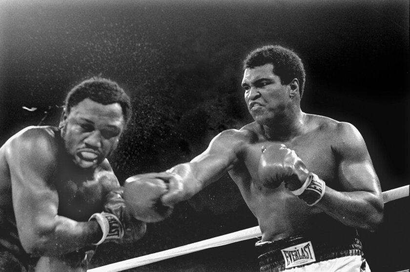 FILE - In this Oct. 1, 1975, file photo, spray flies from the head of challenger Joe Frazier as heavyweight champion Muhammad Ali connects with a right in the ninth round of their title fight in Manila, Philippines. Ali, the magnificent heavyweight champion whose fast fists and irrepressible person