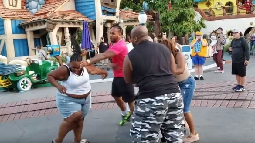 In an image from video, family members scuffle as bystanders watch at Disneyland on July 6.