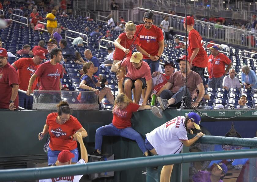 Los aficionados saltan a un pozo de la cámara después de escuchar disparos desde el exterior del estadio