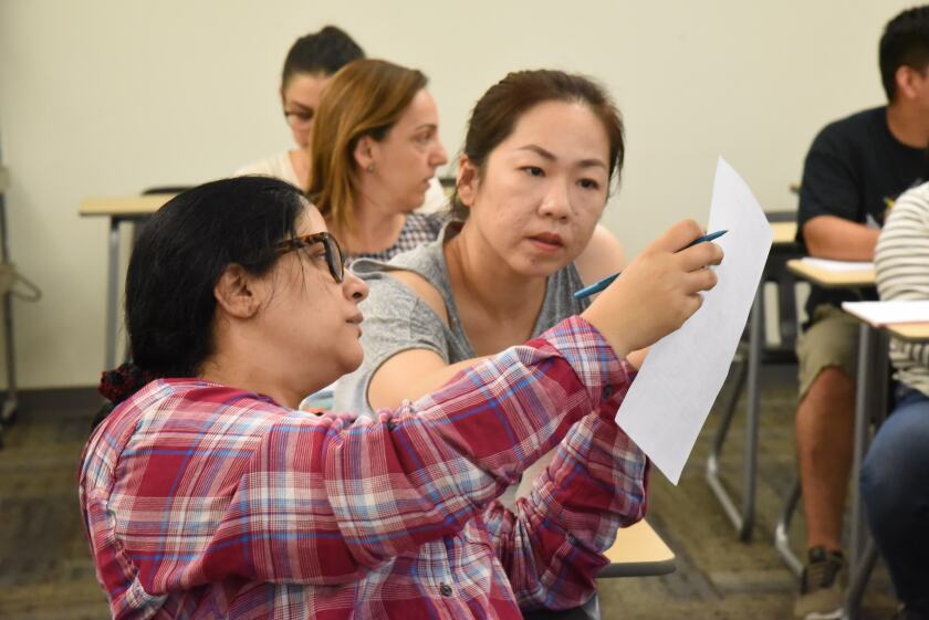 Students Sherin Eltawil, front, and Ruby Lee, behind, discuss a question that Lee had about attendance.