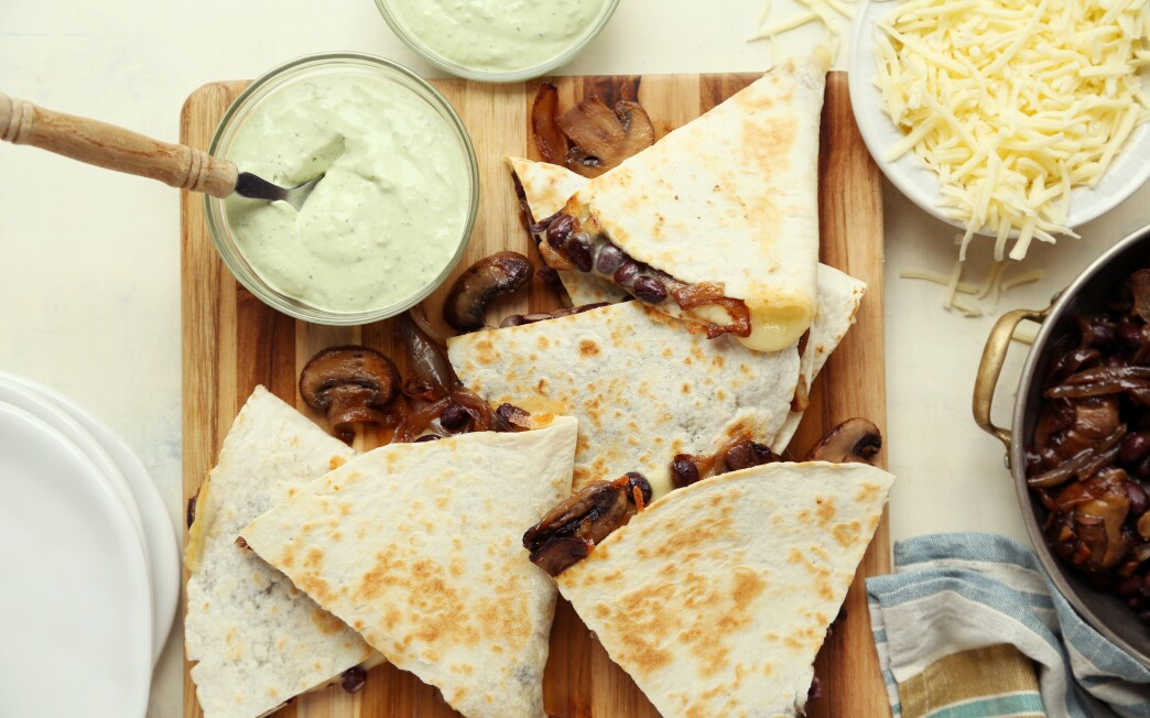 A bright avocado cream adds freshness to these cheesy vegetarian quesadillas teeming with mushrooms and black beans.