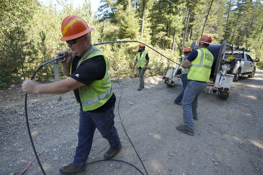 Crews pull fiber optic cable off of a spool