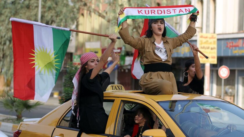 Iraqi Kurdish women celebrate with the Kurdish flag as they ride in a taxi in the northern city of Kirkuk on Sept. 25, 2017.
