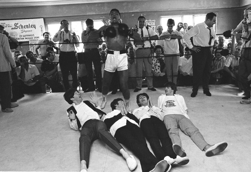 FILE - In this Feb. 18, 1964, file photo, boxer Muhammad Ali, or Cassius Clay at the time, beats his chest in triumph after toppling Britain's Beatles at his training camp in Miam i Beach, Fla. The Beatles, left to right: Paul McCartney; John Lennon; George Harrison and Ringo Starr, were on Holiday