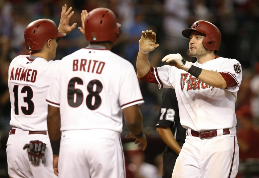 Arizona Diamondbacks A.J. Pollock, right, celebrates with Nick Ahmed and Socrates Brito after hitting a three-run home run against the San Diego Padres during the seventh inning of a baseball game, Tuesday, Sept. 15, 2015, in Phoenix. (AP Photo/Rick Scuteri)