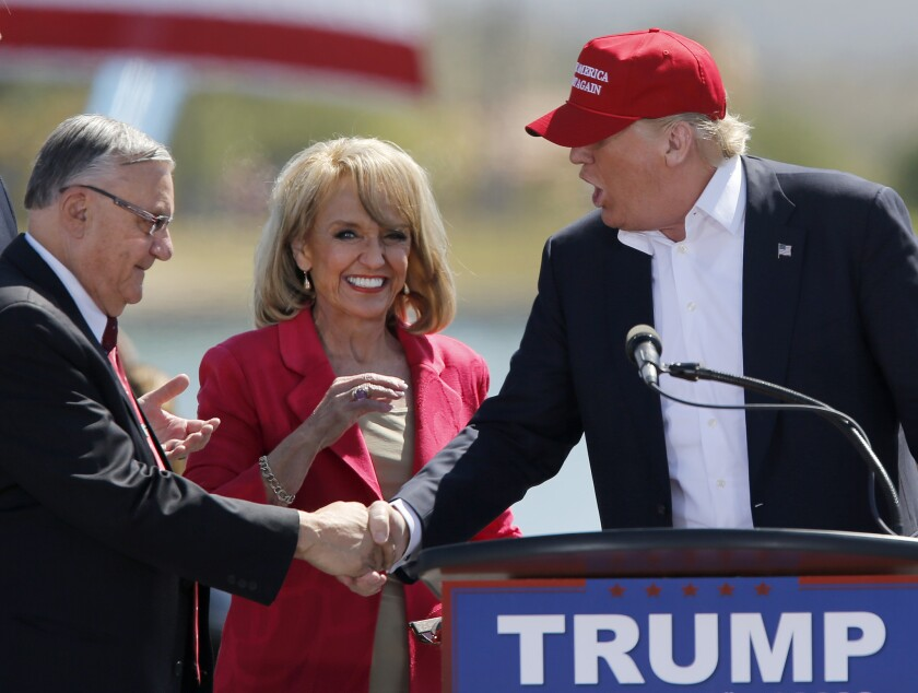 Maricopa County Sheriff Joe Arpaio, left, and former Arizona Gov. Jan Brewer greet Republican presidential candidate Donald Trump at a rally in Fountain Hills, Ariz., on March 19, 2016.
