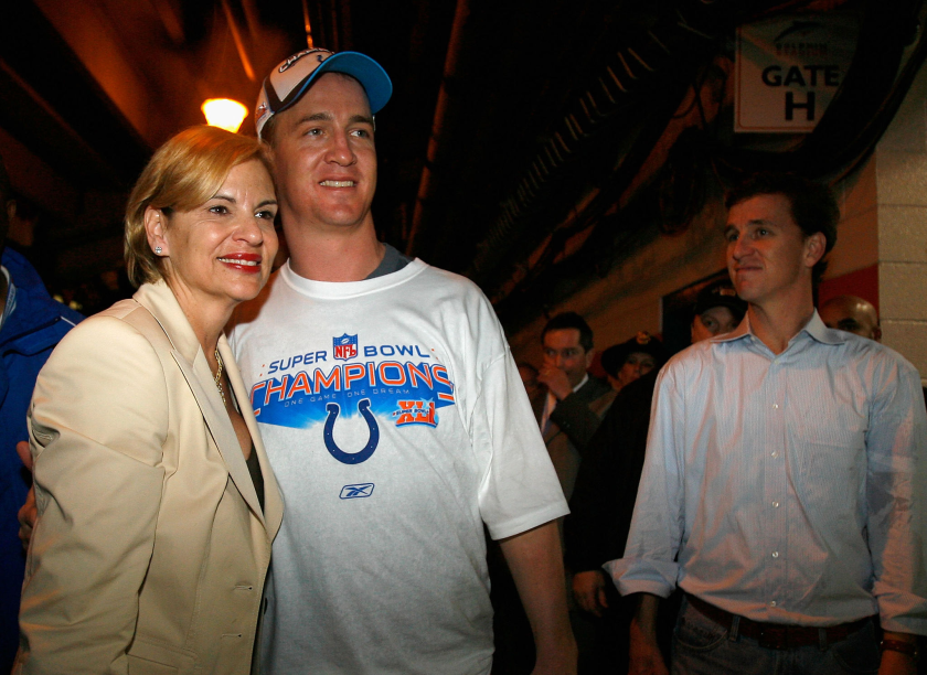 Olivia Manning poses for a photo with her son Peyton Manning while his brother Cooper looks on.