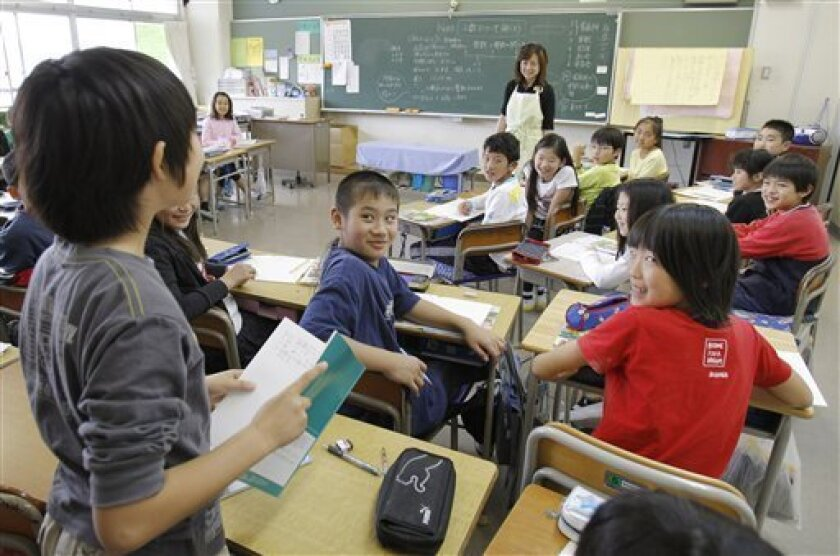 In this photo taken on May 11, 2010, teacher Kazuyo Arai, background standing, and her class listen to a student speaking at Honmoku Elementary School in Yokohama, south of Tokyo. Alarmed that its children are falling behind those in rivals such as South Korea and Hong Kong, Japan is adding about 1,200 pages to elementary school textbooks, bringing the total to nearly 6,100. (AP Photo/Koji Sasahara)