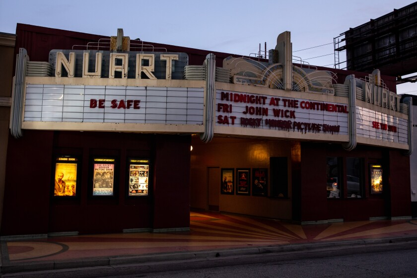 """A theater exterior has a marquee that says """"Be safe"""""""