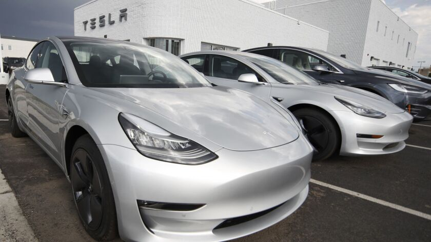 """Model 3 sedans sit on display outside a Tesla showroom in Colorado in July. Tesla CEO Elon Musk acknowledged Sunday that the company is now in """"delivery logistics hell."""""""