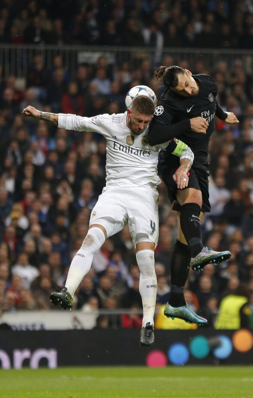 PSG's Zlatan Ibrahimovic, right, fights for the will with Real Madrid's Sergio Ramos during his Group stage of Champions League Group A soccer match against Real Madrid at the Santiago Bernabeu stadium in Madrid, Spain, Tuesday, Nov.3, 2015. (AP Photo/Daniel Ochoa de Olza)