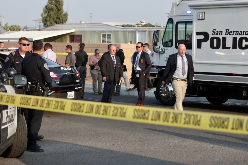 People stand behind crime scene tape