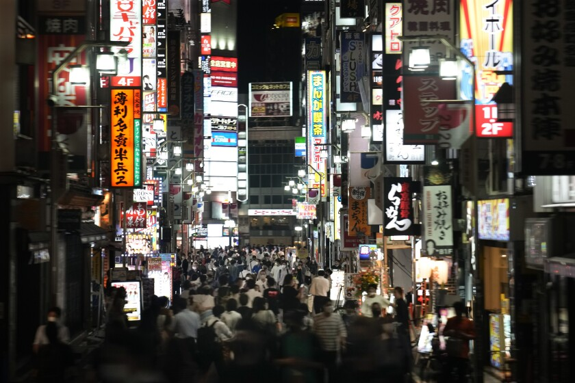 FILE - In this July 16, 2021, file photo, people crowd the street in the Kabukicho area, Tokyo's entertainment district. Japan is now in its fourth state of emergency. Restaurants and bars are asked to close early and can't serve alcohol. (AP Photo/Jae C. Hong, File)