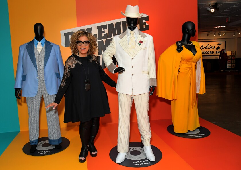 """Costume designer Ruth E. Carter stands with her costumes from """"Dolemite Is My Name"""""""