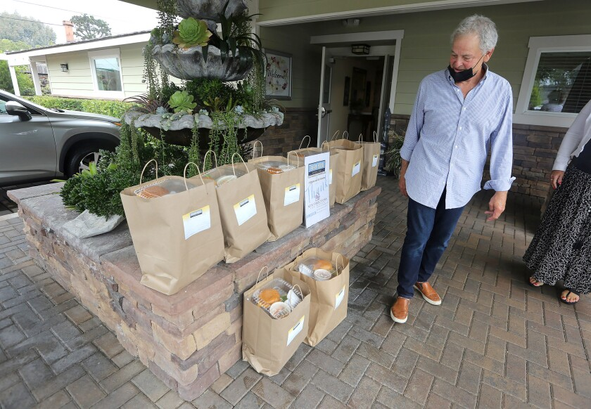Tavern House Kitchen + Bar co-owner Gregg Solomon oversees delivery of pre-packaged lunches from the restaurant to the New Directions for Women facility in Costa Mesa on Monday.