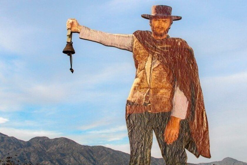 "The artist behind this public art piece, a plywood cutout portraying Clint Eastwood in ""A Fistful of Dollars"" installed on a Glendale-area hiking trail, added a bell and an inscription in tribute to Nicholas Green, a 7-year-old killed by a gunman's bullet while on a family trip to Italy in 1994. The artist learned of the boy's story when he met Nicholas' father on the trail."