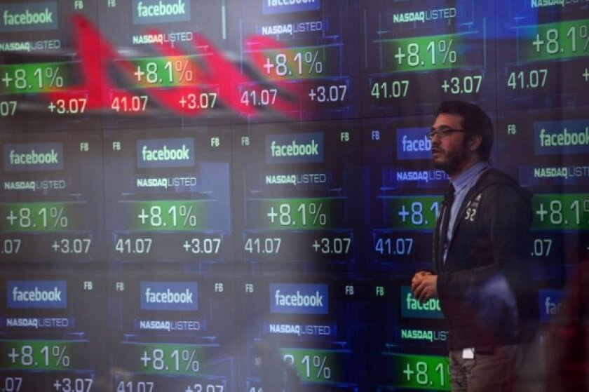 A television anchor stands in front of screens showing the start of trading in Facebook shares on May 18, 2012. Shares were up $1.69, or 4%, to $49.01 on Tuesday. They hit an all-time high of $49.66 earlier in the day.