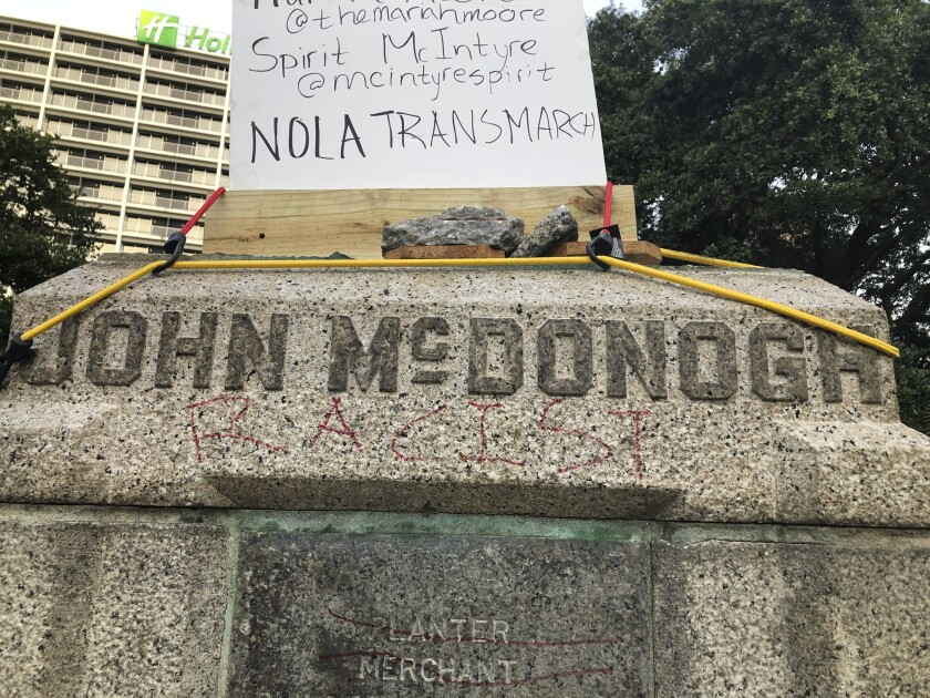 """Demonstrators in New Orleans wrote """"racist"""" and pulled down the bust of John McDonogh, a slave owner."""