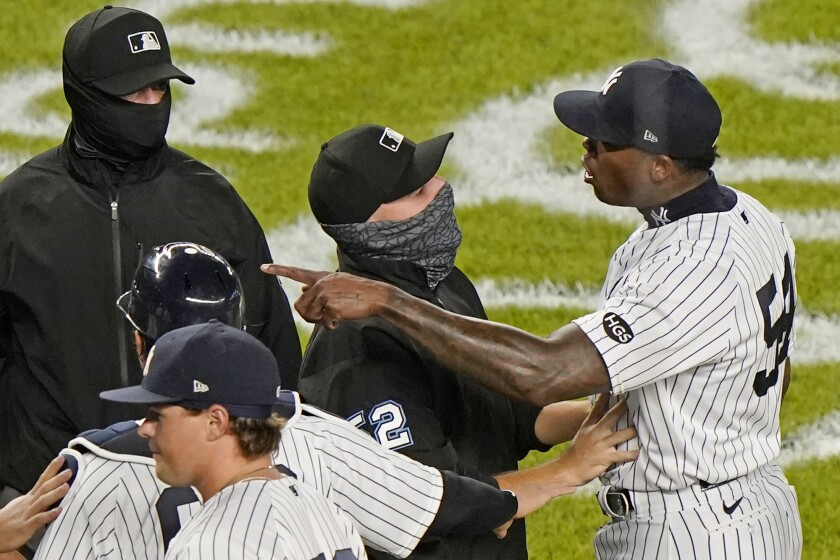 Third base umpire Jansen Visconti, center, restrains New York Yankees relief pitcher Aroldis Chapman, right, after the Tampa Bay Rays and Yankees traded words after the Yankees' 5-3 victory in a baseball game, Tuesday, Sept. 1, 2020, at Yankee Stadium in New York. The altercation ensued after Chapman threw a high pitch at Rays pinch hitter Michael Brosseau in the final at-bat of the game. (AP Photo/Kathy Willens)