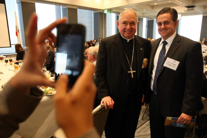 Los Angeles Archbishop Jose Gomez, left, poses for a photo with Jose A. Gomez, vice president and chief of staff at Cal State Los Angeles, before the archbishop delivered a speech on immigration reform at the Rotary Club luncheon at City Club in downtown Los Angeles on Friday.