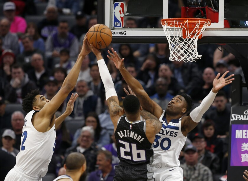 Minnesota Timberwolves center Karl-Anthony Towns, left, blocks the shot of Sacramento Kings guard Kent Bazemore, center, as he goes to the basket against Timberwolves forward Kelan Martin, right, during the first quarter of an NBA basketball game in Sacramento, Calif., Monday, Feb. 3, 2020. . (AP Photo/Rich Pedroncelli)