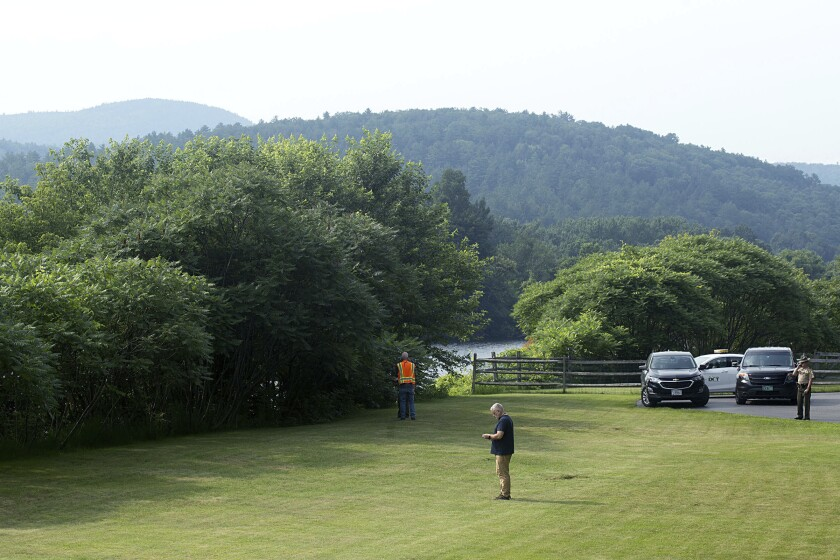 Investigators, including those from the Federal Aviation Administration, gather along the Connecticut River and Route 25 in Bradford, Vt., on Friday, July 16, 2021, following the death of a hot-air ballonist. Brian Boland, 72, the pilot of the hot-air balloon that had been carrying a total of five people, died Thursday, July 15, 2021, after becoming entangled in gear underneath the basket and then falling to the ground in Bradford, Vermont State Police said. Some after take off, the balloon touched down in a field and one passenger fell out, but was unhurt. After the pilot's death, three other passengers remained in the balloon until it caught in a grove of trees about 1.5 miles (2.4 kilometers) farther north in Piermont, New Hampshire, where they escaped without injury. (Geoff Hansen/The Valley News via AP)