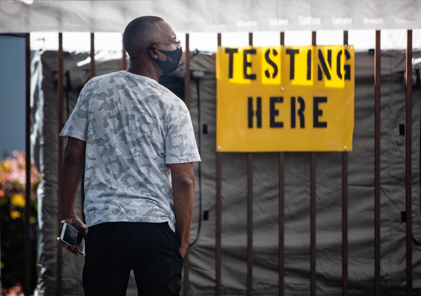 A man waits outside Kedren Community Health Center in South Los Angeles where walk-up coronavirus testing was offered Tuesday.