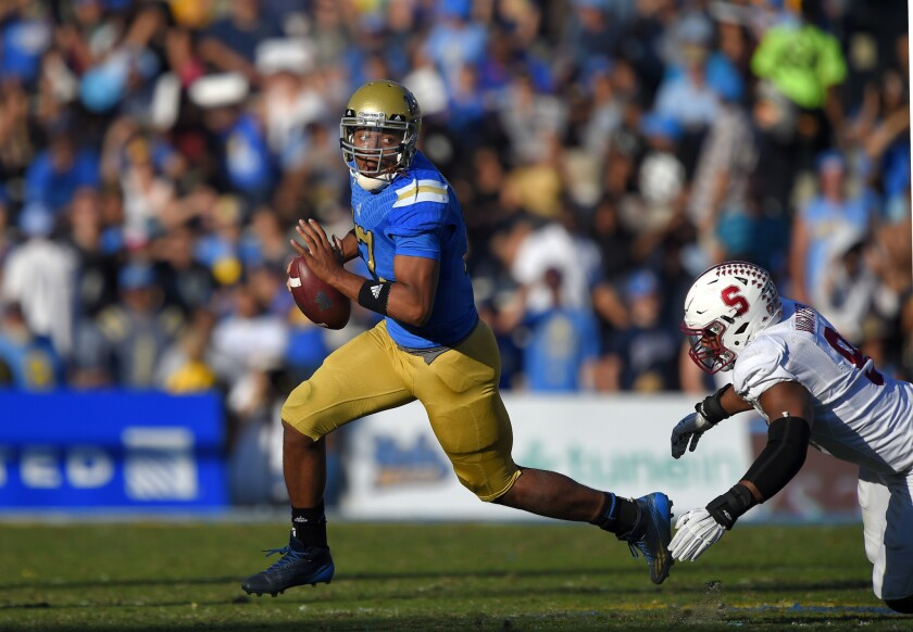 UCLA quarterback Brett Hundley escapes a tackle by Stanford linebacker James Vaughters at the Rose Bowl on Nov. 28, 2014.