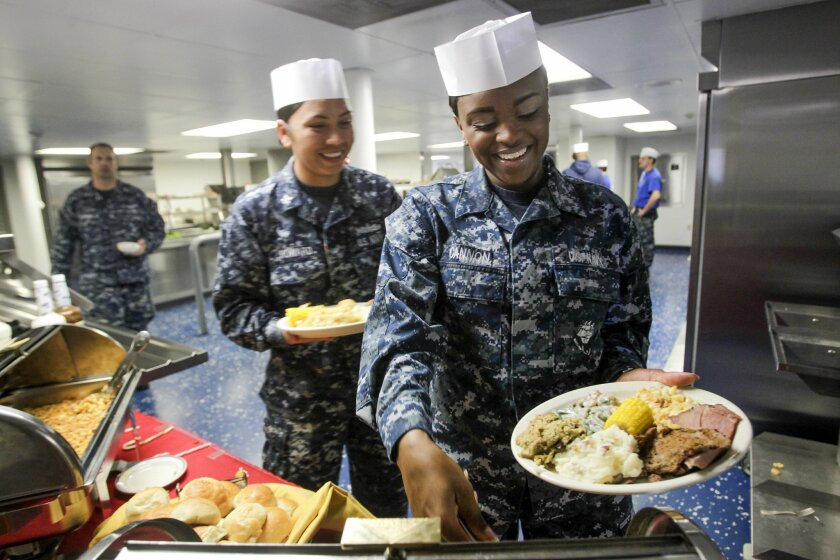 Navy cooks Kyla Cannon, right, and Nicole Howard add to their plates full of food.