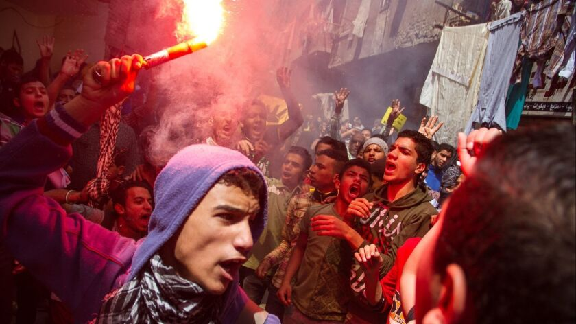 FILE - In this Friday, April 24, 2015 file photo, an Egyptian youth carries a lit flare as supporter