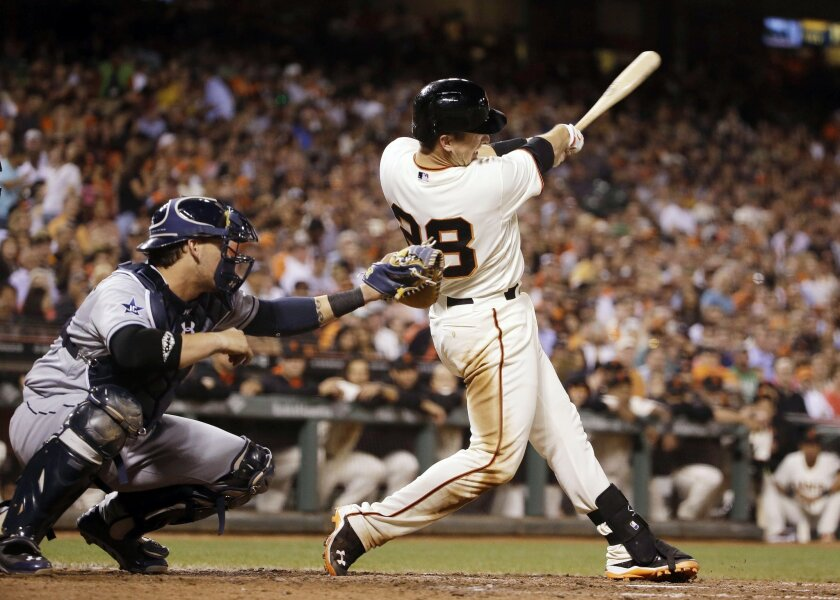 San Francisco Giants' Buster Posey, right, hits an RBI single off San Diego Padres relief pitcher Dale Thayer in the seventh inning of a baseball game Wednesday, April 30, 2014, in San Francisco. At left is Padres catcher Yasmani Grandal. (AP Photo)