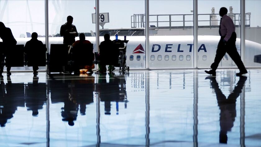 FILE - In this Thursday, Oct. 13, 2016, file photo, a Delta Air Lines jet sits at a gate at Hartsfie