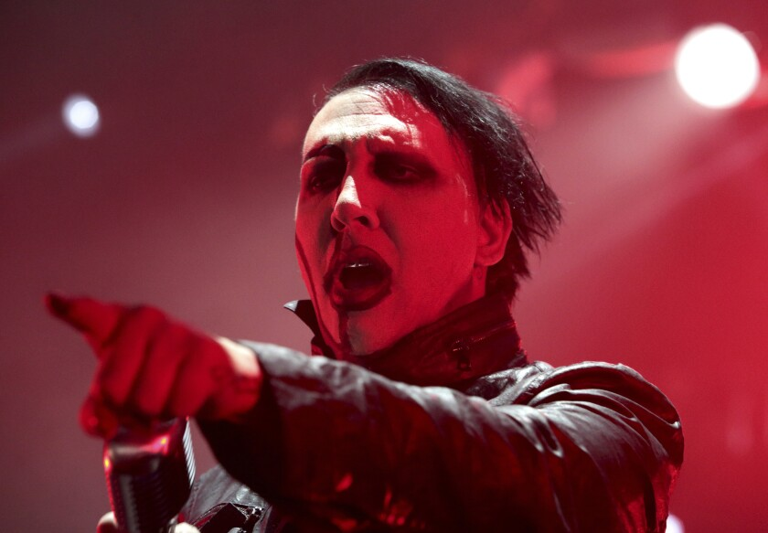 A man in black and white face makeup and red lighting pointing