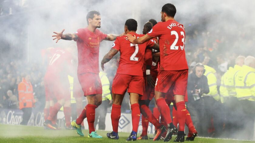 In a haze from a lit flare, Sadio Mane and Liverpool teammates celebrate their first goal in a match against Everton at Goodison Park on Dec. 19.