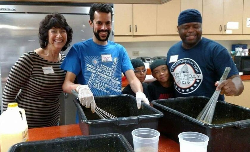 Volunteers participate in an interfaith gathering, preparing 1,000 meals for area homeless. Center is one of the event coordinators, Issam Lagrichi.