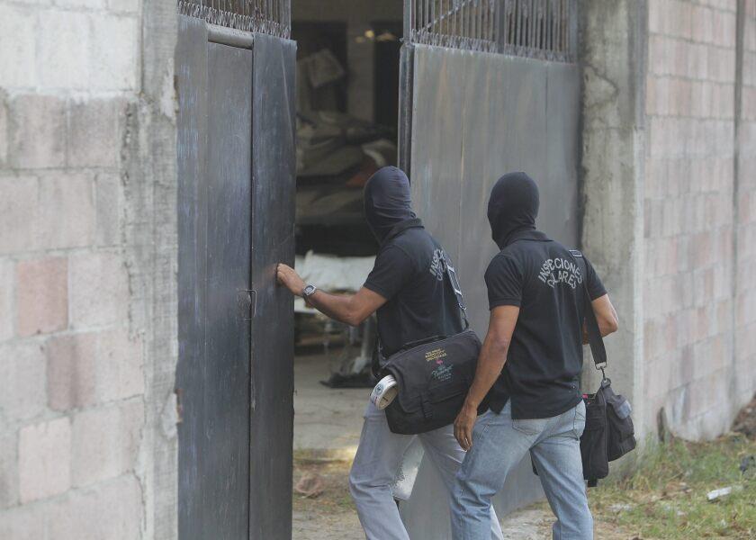 Agentes de Inspección Ocular de la Policía Nacional Civil (PNC) entran a la escena de un crimen.