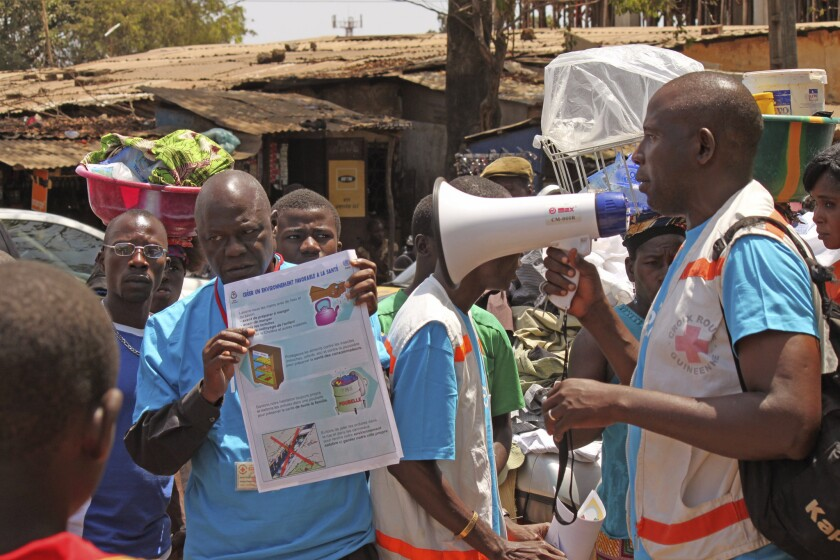 Health workers in Conakry, Guinea, teach people about the Ebola virus and how to prevent infection in March.