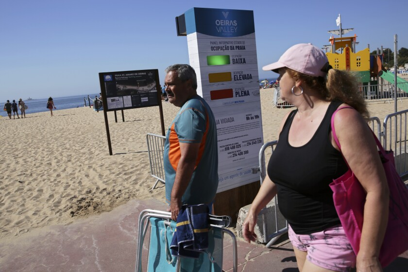 People arriving at the beach walk past a semaphore system that signals how crowded the beach is at any moment, in Oeiras, outside Lisbon, Wednesday, July 15, 2020. The system uses radar to count people entering the gates to the fenced beach to help beachgoers keep social distancing due to the coronavirus pandemic. (AP Photo/Armando Franca)