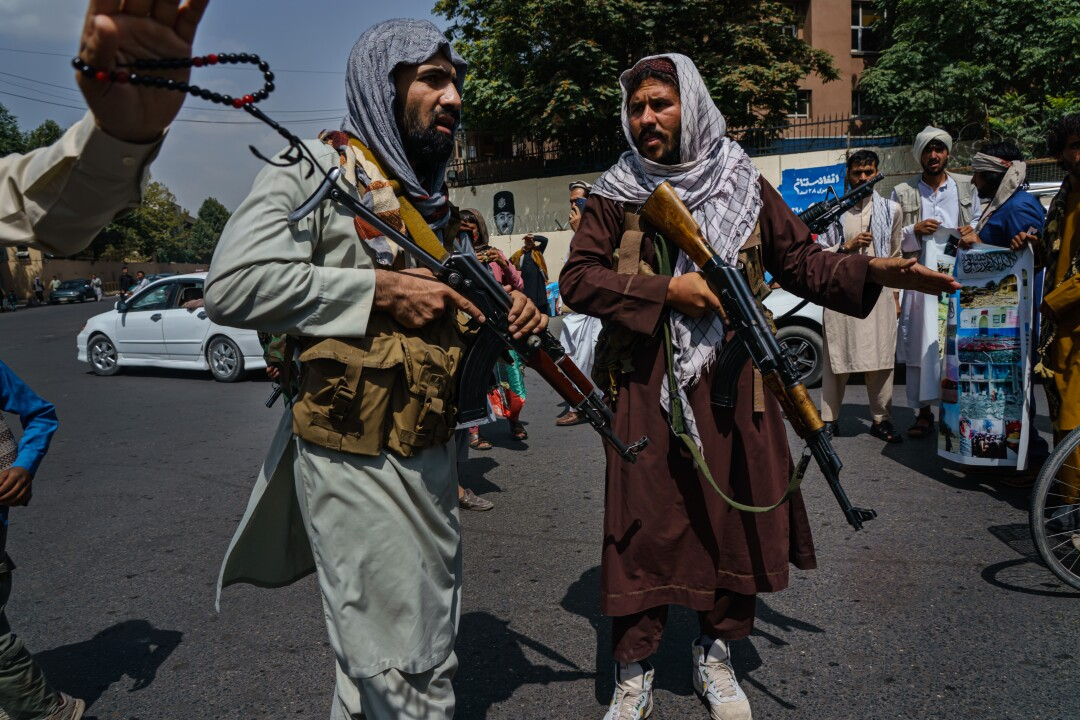 Taliban fighters mobilize to control a crowd.