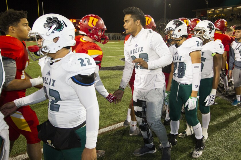 Injured Helix running back  Ezekiel Now (30) shakes hands with the Dons after Cathedral's victory in the Open Division championship.