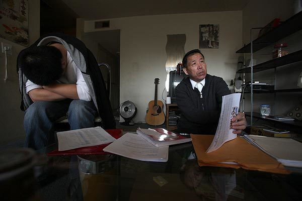 George Shi looks over paperwork as his son Will sits nearby in their San Gabriel home, from which they are working tirelessly to bring the killer of their daughter and sister Donglei to justice.