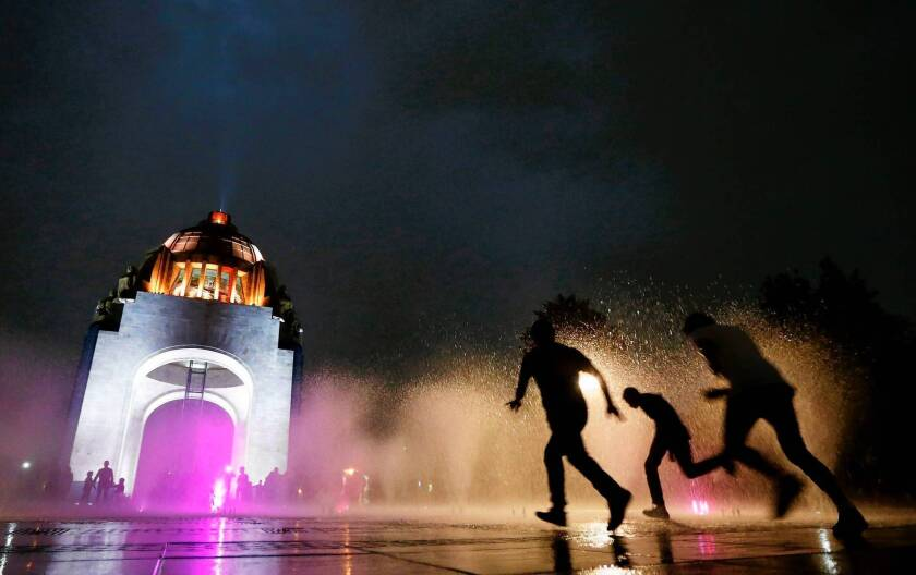 People run through a fountain in front of the illuminated Revolution Monument in Mexico City. The city's water woes could be eased by an aquifer discovered a mile under the neighborhood of Iztapalapa.