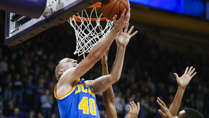 UCLA center Thomas Welsh (40) attempts a reverse layup against Washington in the first overtime Friday.