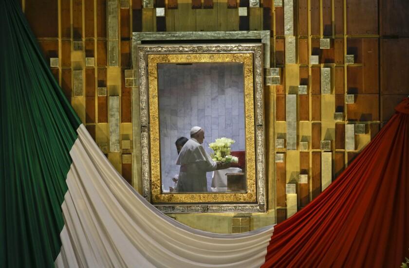 El papa Francisco, reflejado en el marco que contiene la imagen de la Virgen de Guadalupe, sostiene un ramo de flores mientras reza dentro de la basílica construida en su honor en Ciudad de México, el sábado 13 de febrero de 2016. Este es el santuario mariano más importante del mundo y para el pontífice, el primero latinoamericano, era muy importante visitarlo. (Foto AP/Gregorio Borgia)