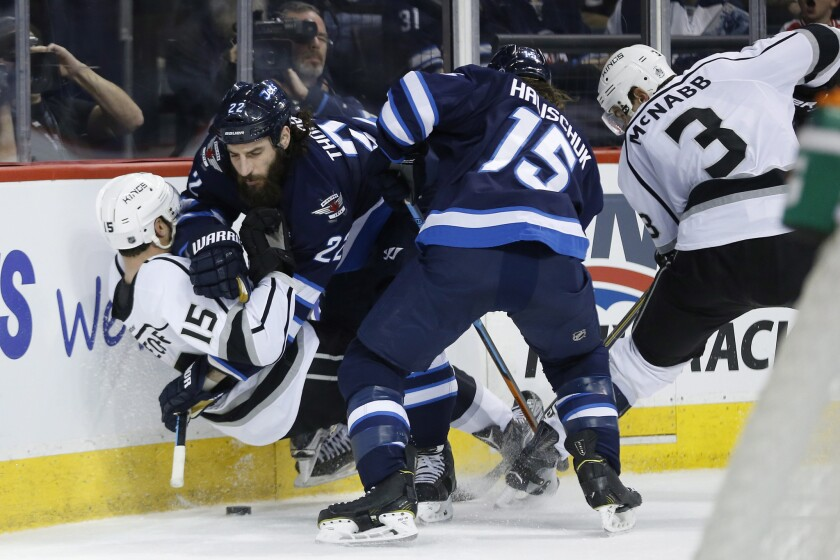 Jets right wing Chris Thorburn (22) takes down Kings left wing Andy Andreoff (15) as Jets' Matt Halischuk (15) and Kings' Brayden McNabb (3) battle for the loose puck during the second period.