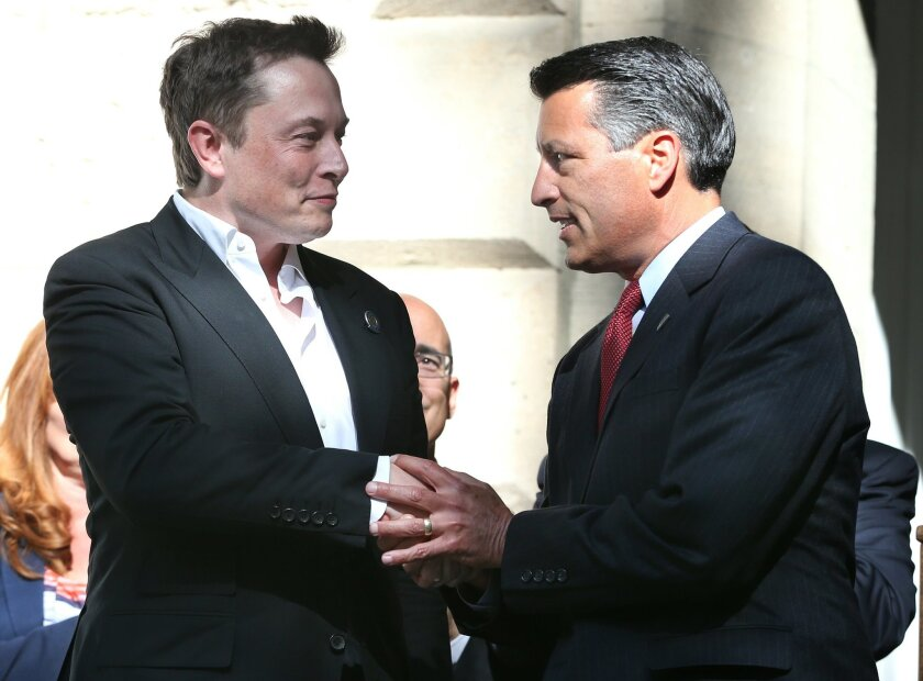 Tesla Motors CEO Elon Musk, left, and Nevada Gov. Brian Sandoval shake hands following a press conference where Nevada was announced as the new site for a $5 billion car battery gigafactory, at the Capitol in Carson City, Nev., on Thursday, Sept. 4, 2014. (AP Photo/Cathleen Allison)