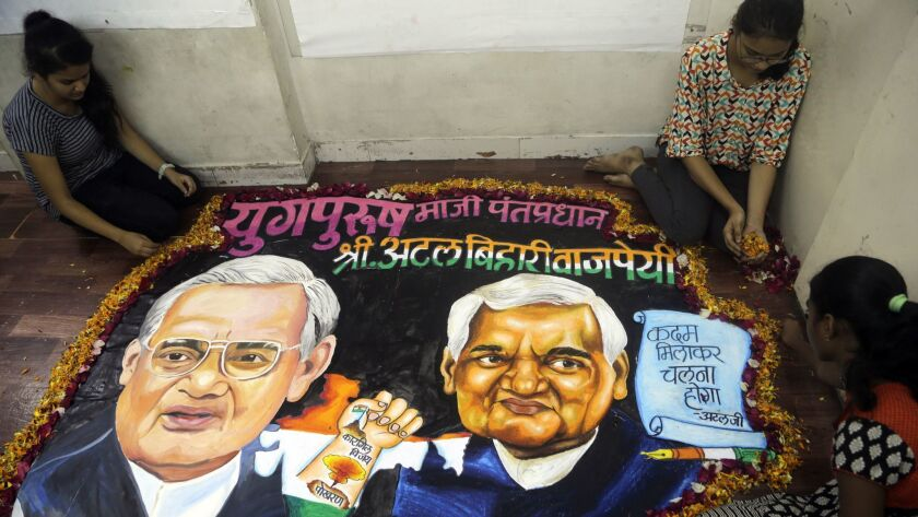 Students from an art school place flower petals around a painting of former Indian Prime Minister Atal Bihari Vajpayee in Mumbai, India, on Thursday.