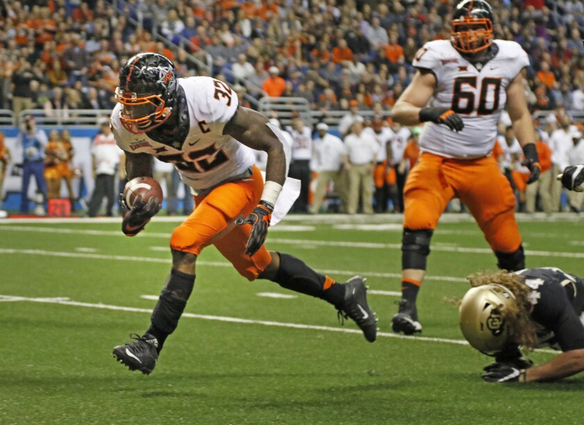 Oklahoma State's Chris Carson (32) eludes the tackle of Buffaloes linebacker Addison Gillam (44) for his team's first touchdown in the Valero Alamo Bowl on Dec. 29.