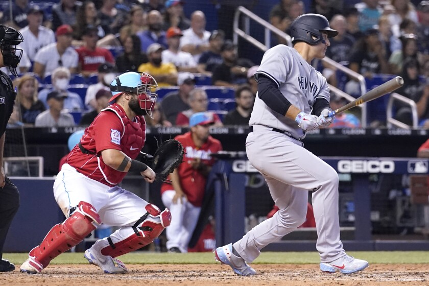 New York Yankees' Anthony Rizzo, right, watches after hitting a single to score Brett Gardner during the eighth inning of a baseball game, Sunday, Aug. 1, 2021, in Miami. Marlins catcher Sandy Leon, second from right, looks on. (AP Photo/Lynne Sladky)